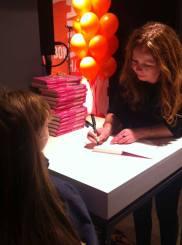 A. Audhild Solberg signerer bøker for noen av jurymedlemmene under utdelinga av ARKs barnebokpris 2014. Foto: Aschehoug
